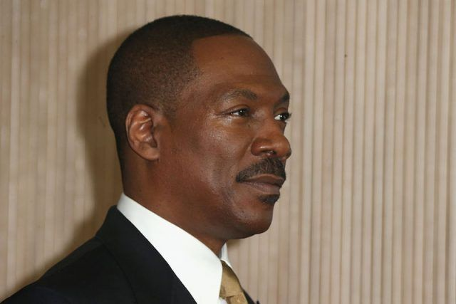 Eddie Murphy smiling in front of a curtain as he stares straight ahead.