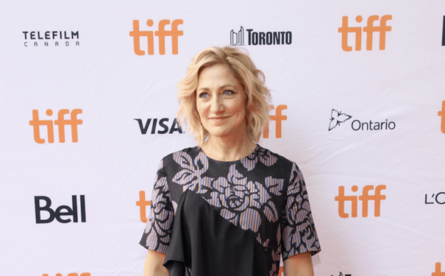 Edie Falco smiling and standing with her arms at her sides while wearing a black floral dress.