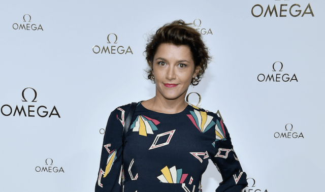 Emma de Caunes standing in a colorful dress with her hand on her hip.