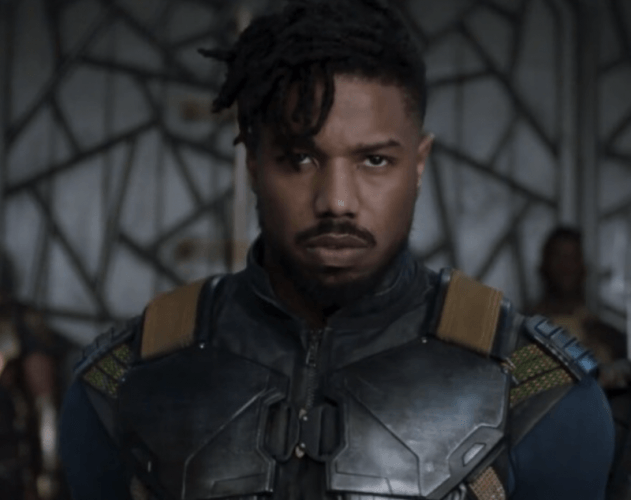 Erik Killmonger stands straight and looks forward while wearing an armored uniform.