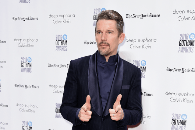 Ethan Hawke posing for photographers while wearing a tuxedo.
