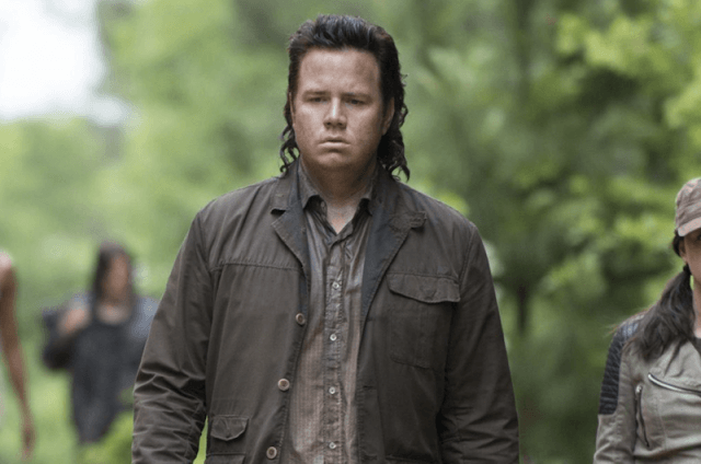 Eugene Porter walking and staring downward at the ground.