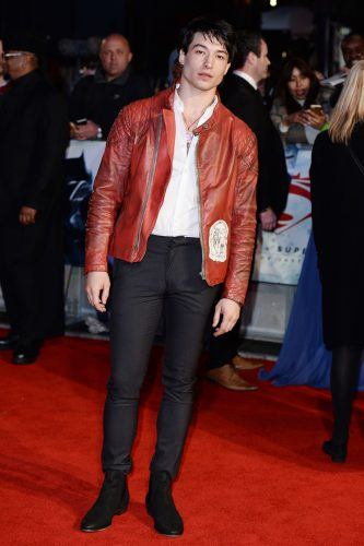 Ezra Miller wearing a red jacket and black pants at a movie premiere red carpet.