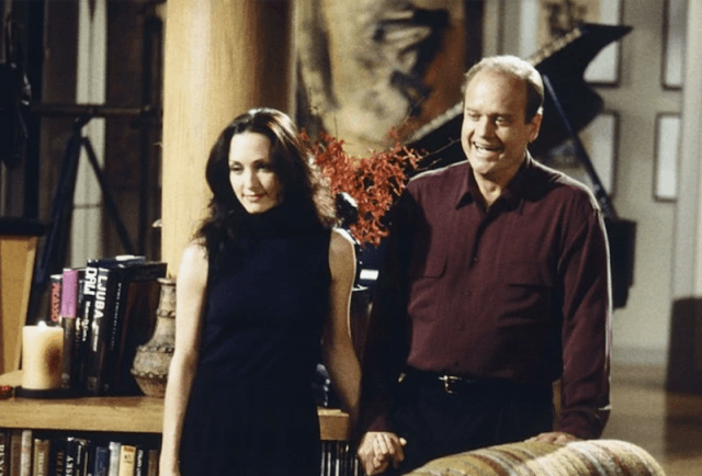 Fraiser standing in his living room with Lillith.