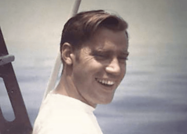 Fred smiles while posing on a boat.
