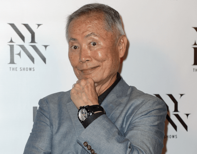 George Takei posing at a fashion show wearing a watch and gray jacket.