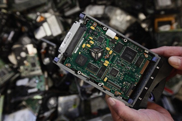 a computer hard drive in front of scrap metal