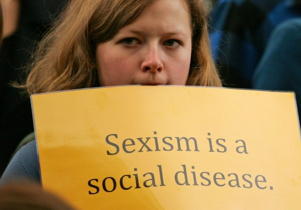 a woman holds a yellow sign reading sexism is a social disease