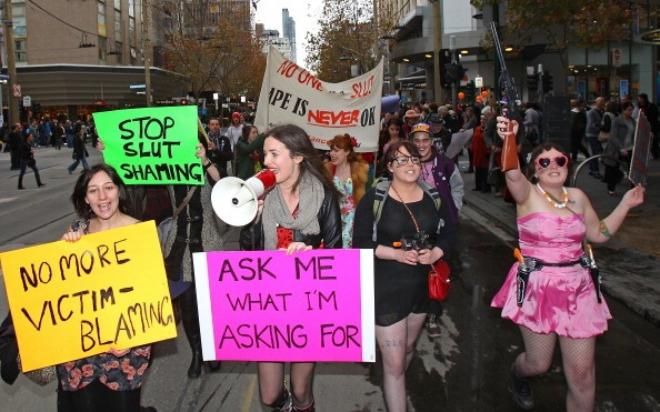 protesters march with signs in yellow, pink, and green