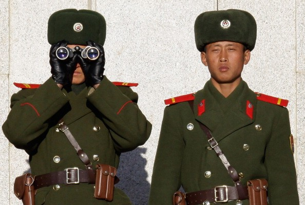 Two North Korea guards in green uniforms with binoculars.