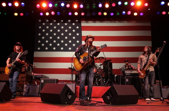 Kid Rock playing guitar against an American flag background