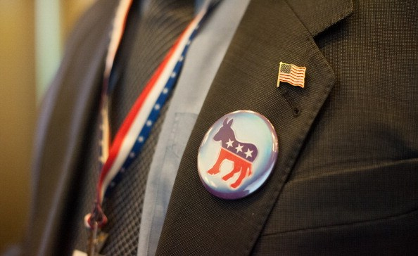a donkey Democrat badge and American flag lapel pin on a dark suit jacket and a red, white and blue lanyard