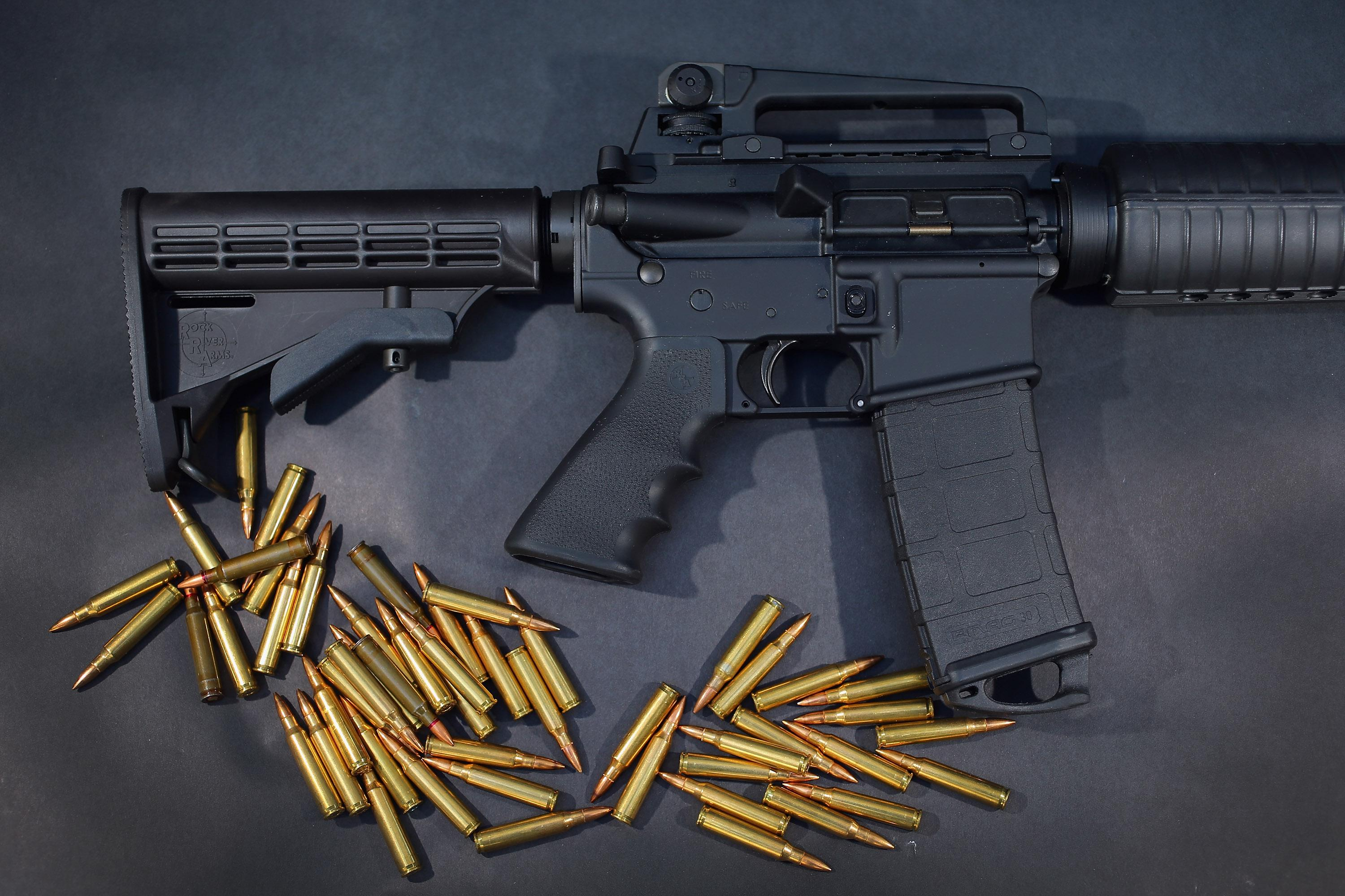 an AR-15 rifle with ammunition on black background