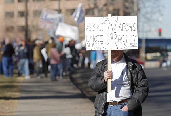 an activist holding a gun sign