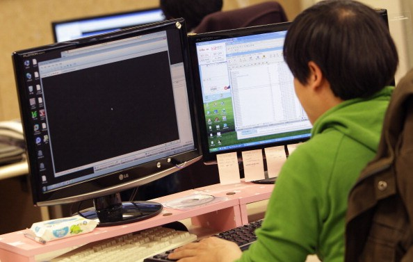 a man in green sitting at a computer with two screens