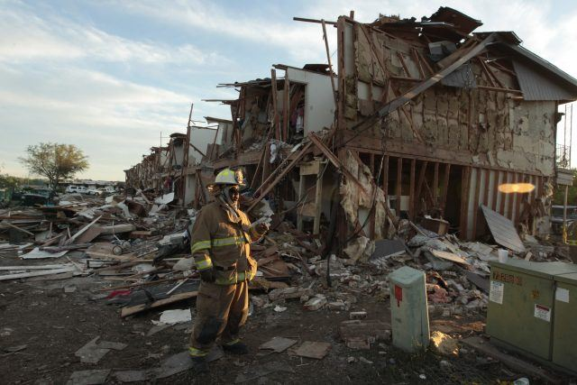 A firefighter stands among a destroyed building caused by an explosion