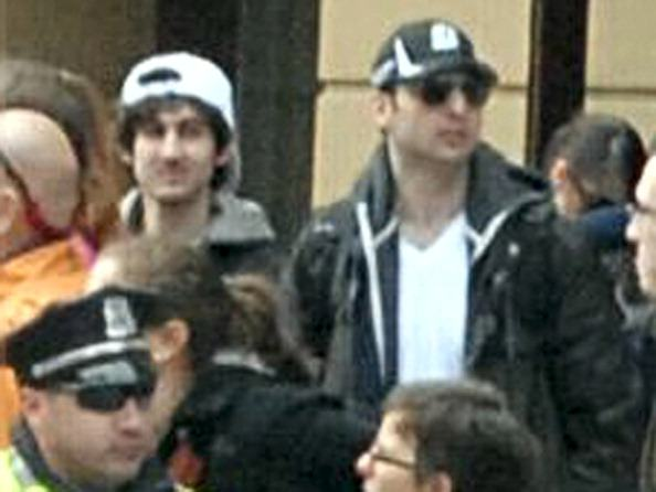 two Boston bombing suspects in a crowd behind a policeman