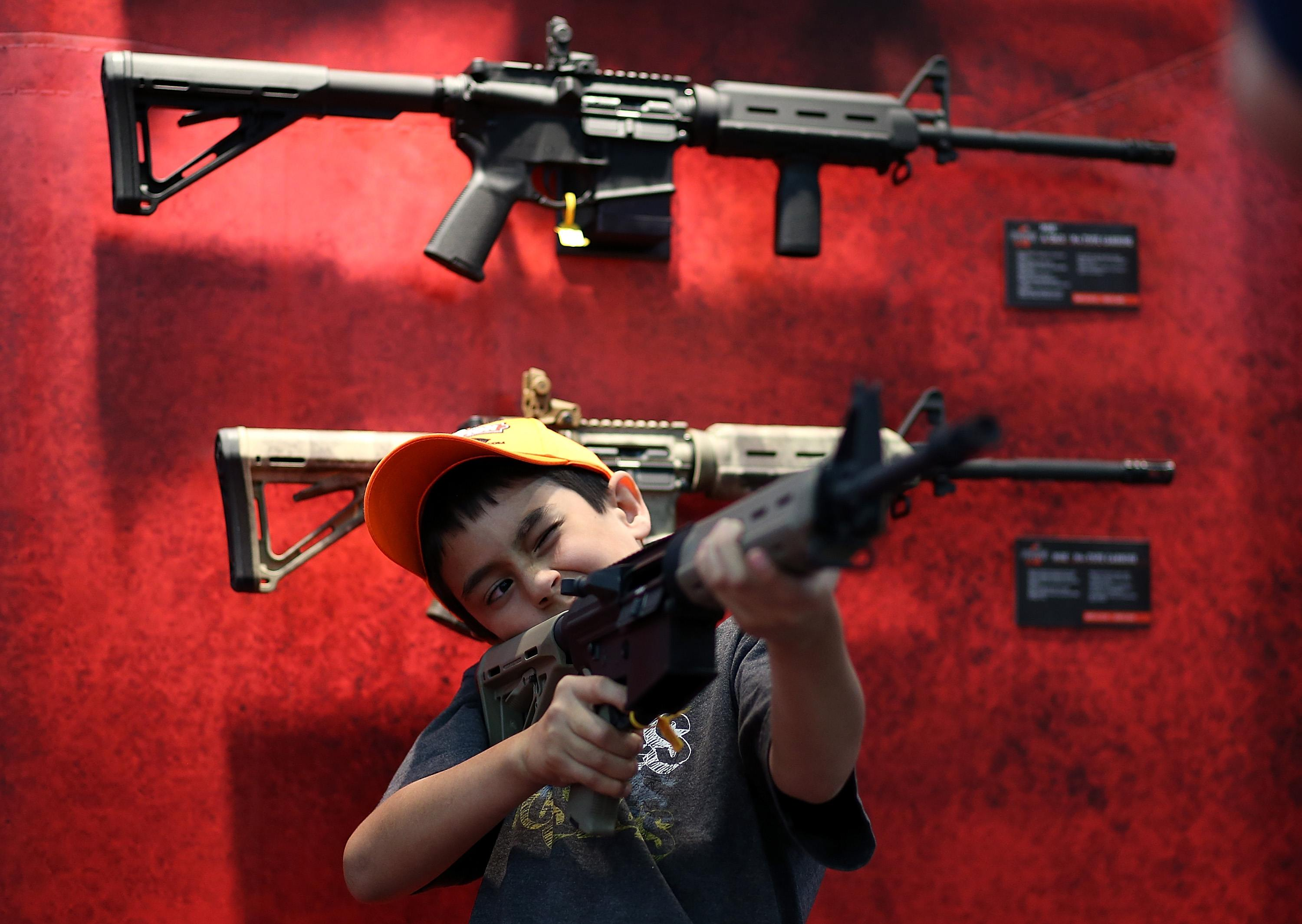 a child tries out an assault rifle against a red display with guns