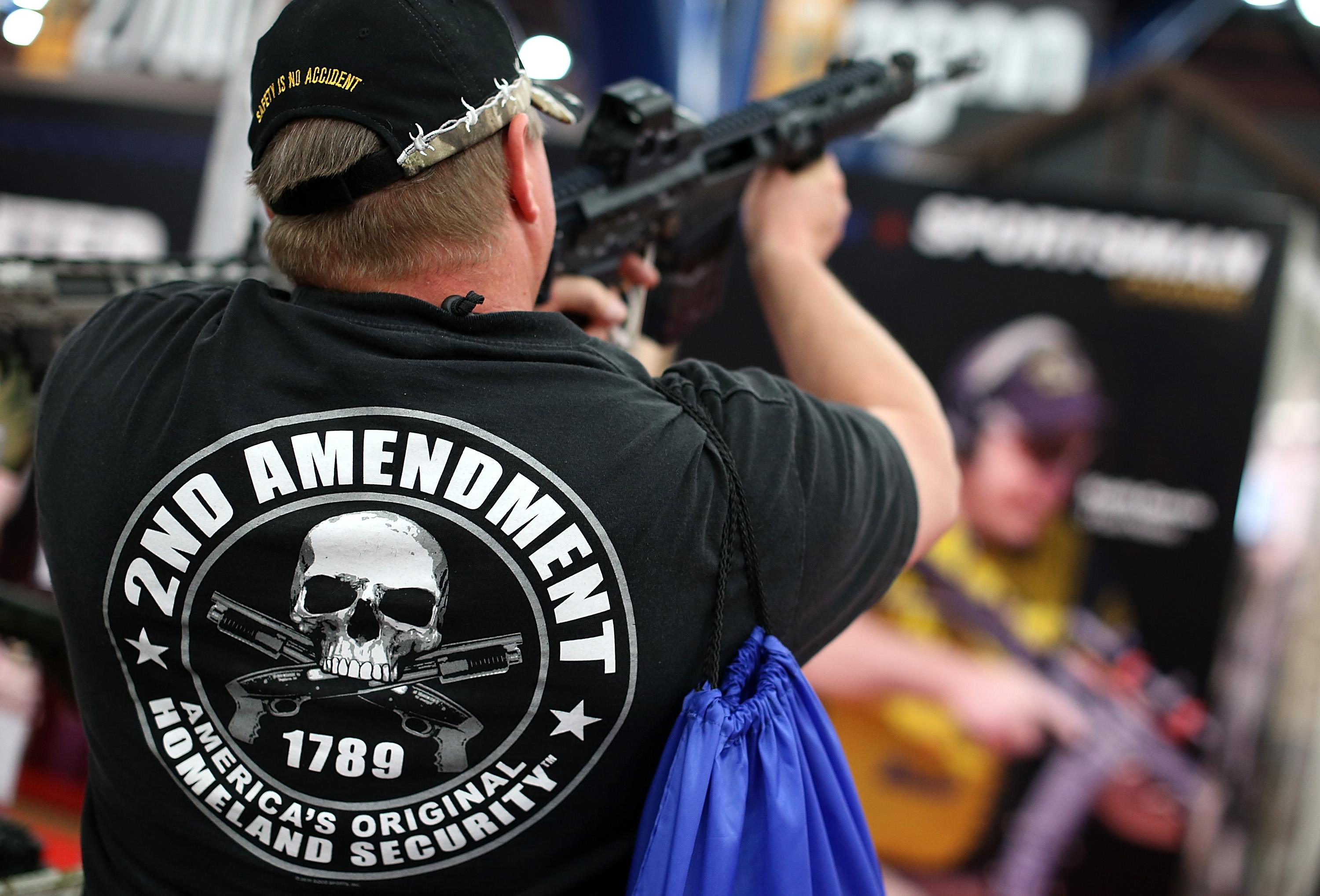 An attendee wears a 2nd amendment shirt while inspecting an assault rifle during the 2013 NRA Annual Meeting and Exhibits at the George R. Brown Convention Center