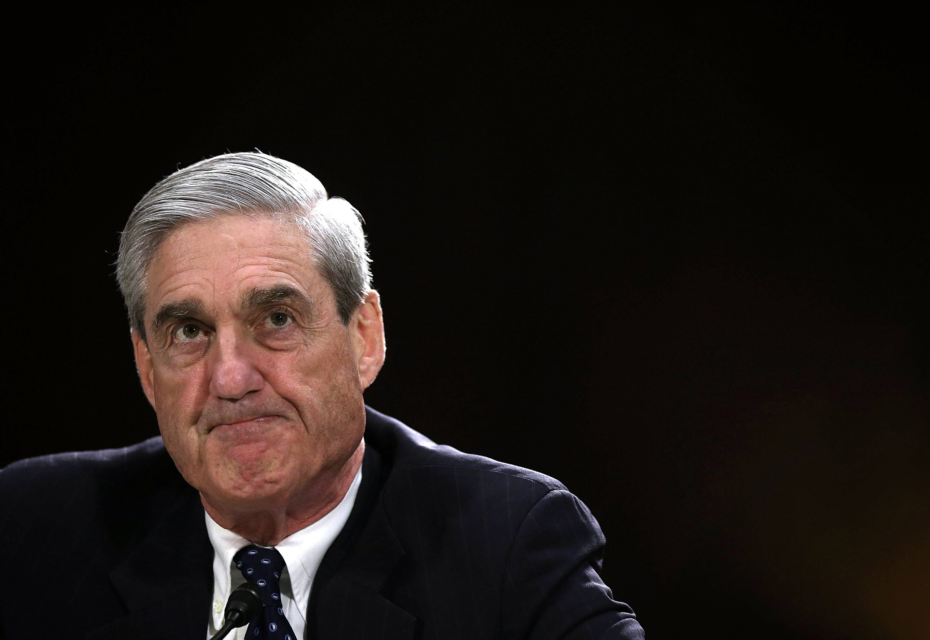 robert mueller in a dark suit and a dark tie against a black background