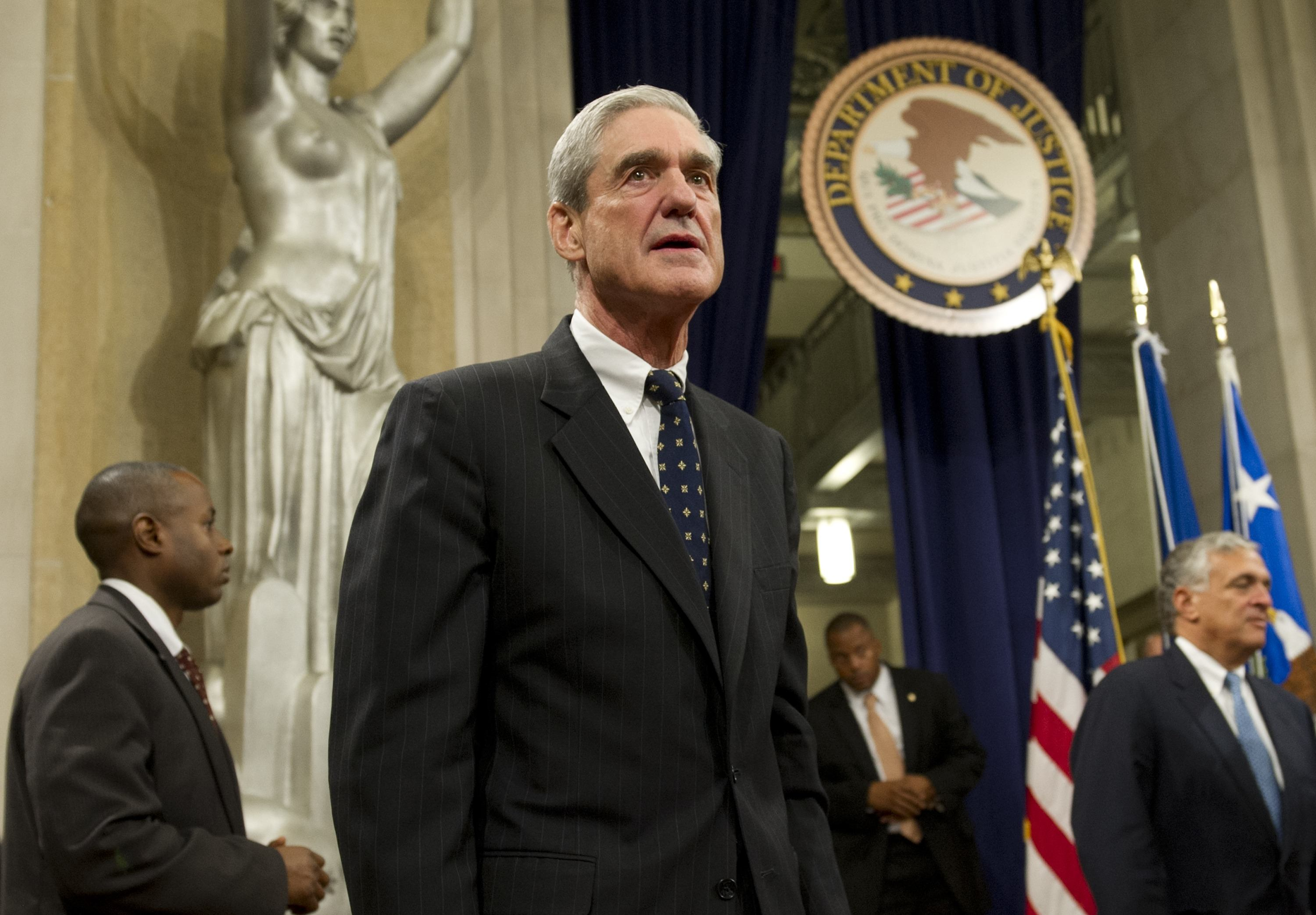 Robert Mueller standing in front of a statue of lady justice and the seal of the Department of Justice.
