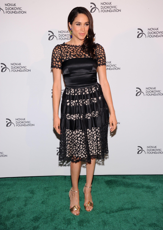 Meghan Markle posing on a green carpet in a black crochet dress