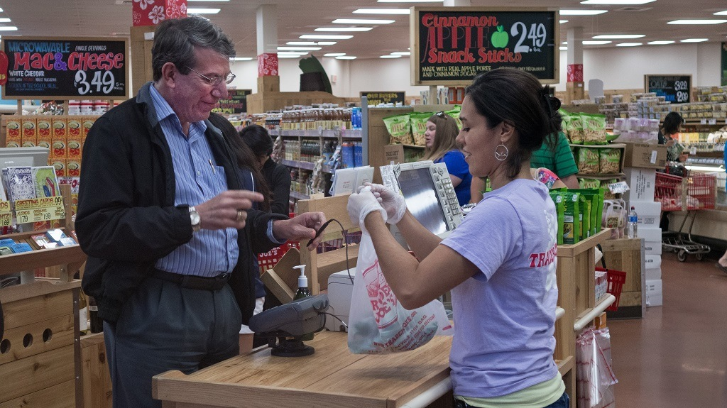 "An unidentified man (L) pays for groceries at Trader Joe's in Centreville, Virginia, on September 13, 2013. The national supermarket chain informed part-time employees that it would end health insurance benefits in 2014 for employees who work less than 30 hours a week, sending them instead to the new public insurance marketplaces with an extra 500 USD to help purchase coverage. Under the Affordable Care Act (ACA), or ""Obamacare"", companies are not required to offer health coverage to their part-time workers. AFP PHOTO/Paul J. Richards (Photo credit should read PAUL J. RICHARDS/AFP/Getty Images)"