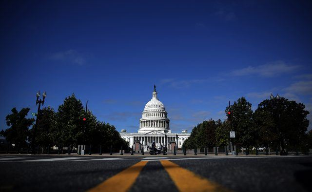 A Road leads directly to the United States capitol Building with green trees abutting each side of the photo on a sunny day