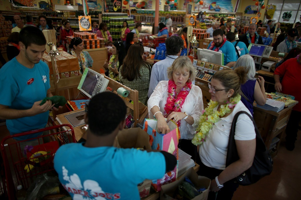 Kimberly Davison (L) and Elena Evans pay for their groceries as they attend the grand opening of a Trader Joe's on October 18, 2013 in Pinecrest, Florida. Trader Joe's opened its first store in South Florida where shoppers can now take advantage of the California grocery chains low-cost wines and unique items not found in other stores. About 80 percent of what they sell is under the Trader Joe's private label. (Photo by Joe Raedle/Getty Images)