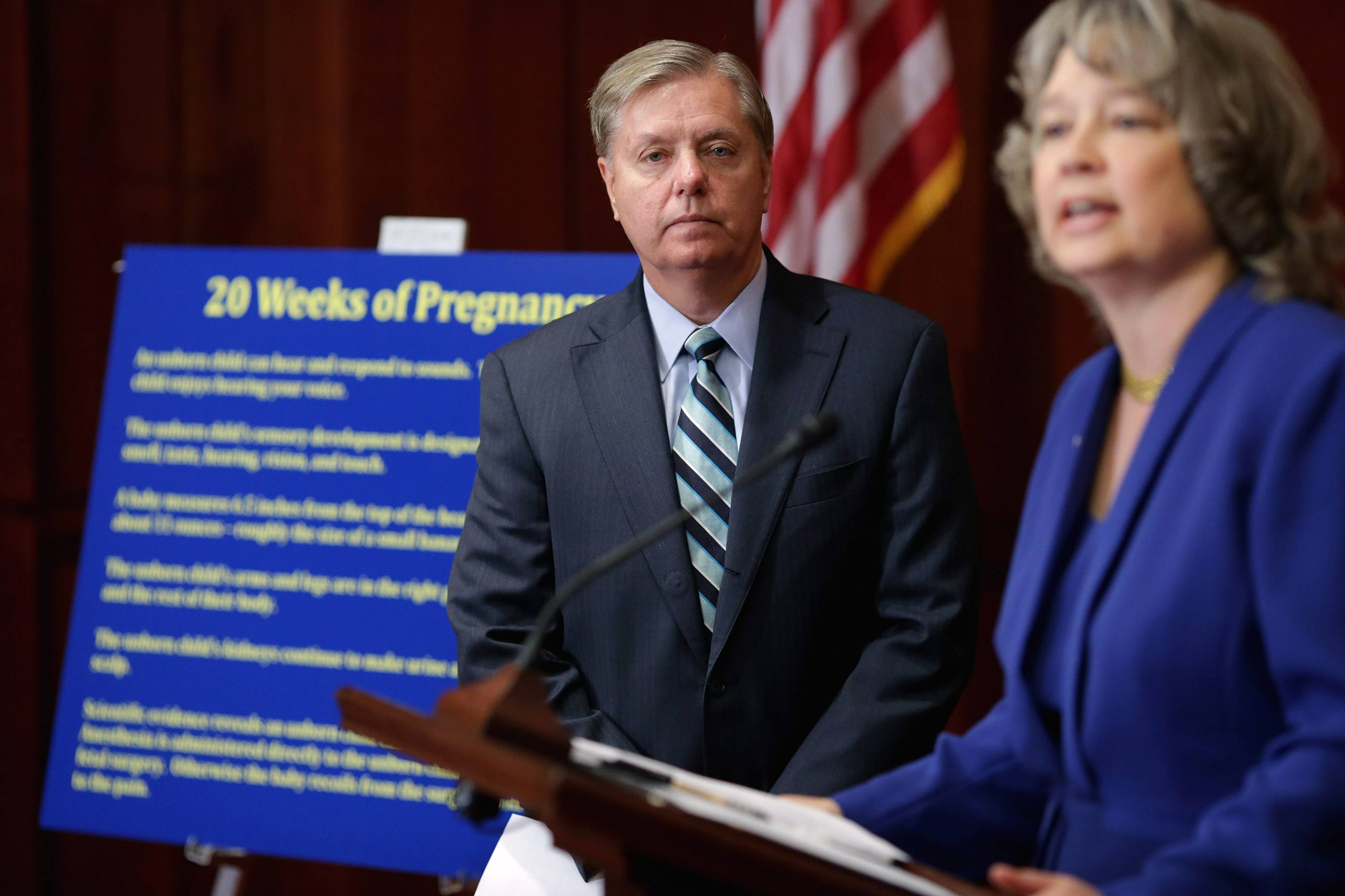 Sen. Lindsey Graham (R-SC) (L) listens to National Right to Life Committee President Carol Tobias speak while standing infront of a board that explains the Pain-Capable bill of banning abortions after 20 weeks