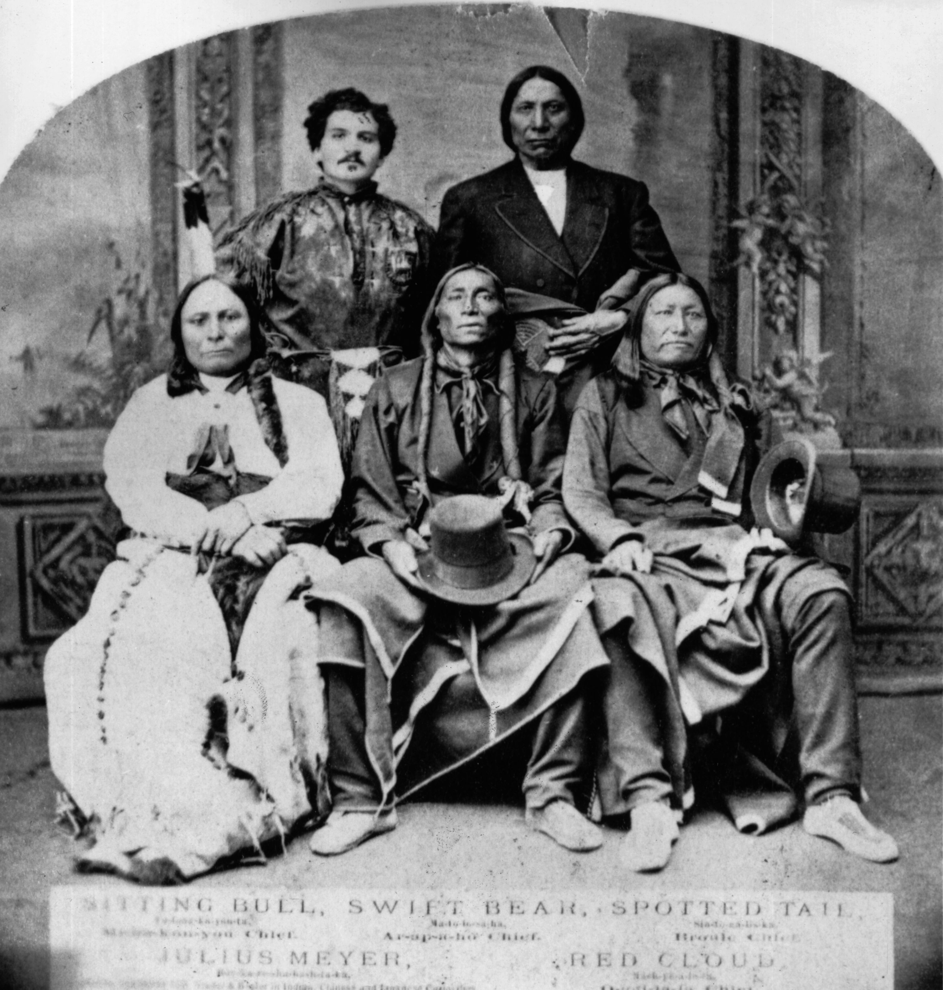 Sitting Bull sits with three other Native Americans and their interpreter