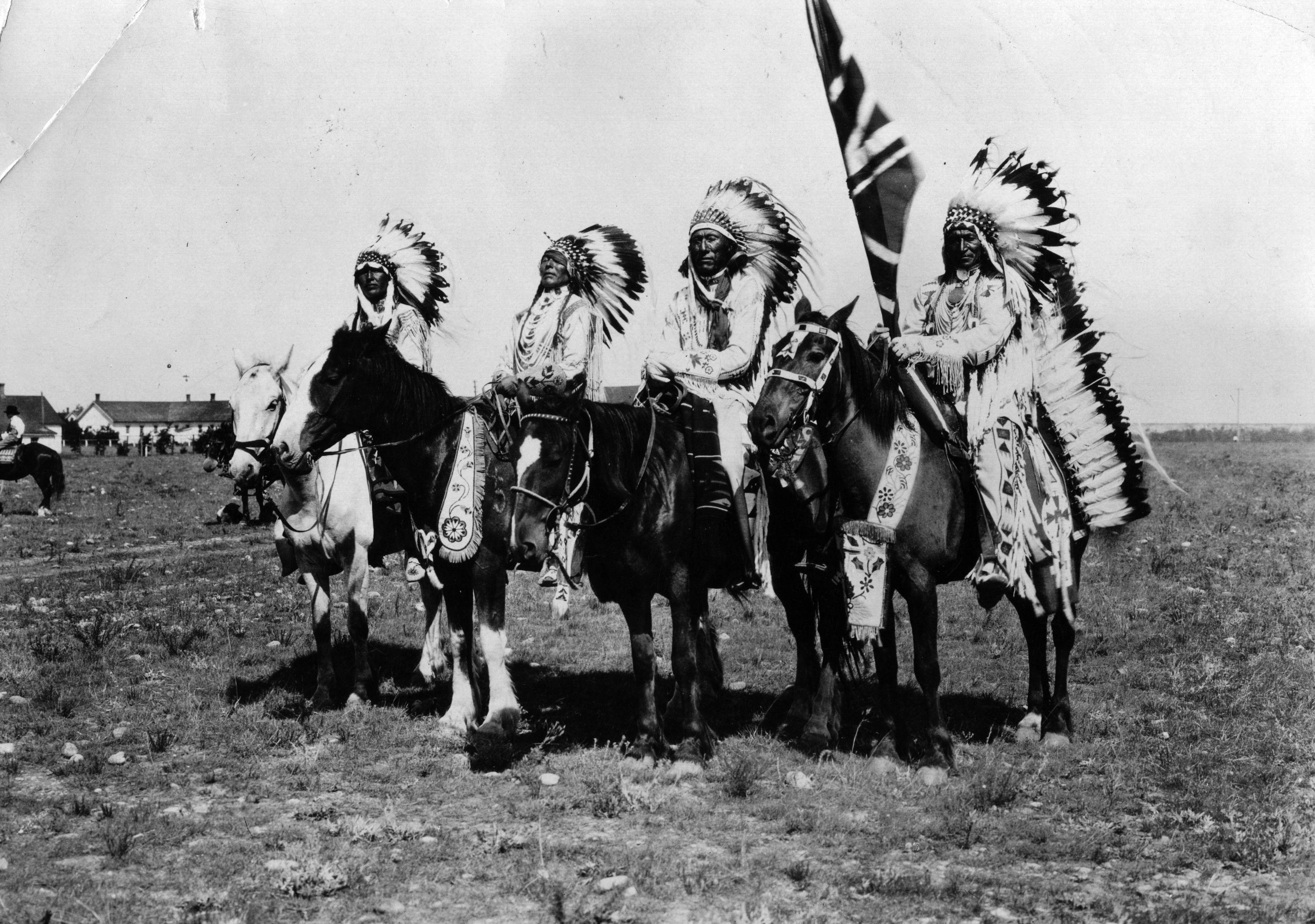 Native chiefs on horseback, wearing long, feathered headdresses.