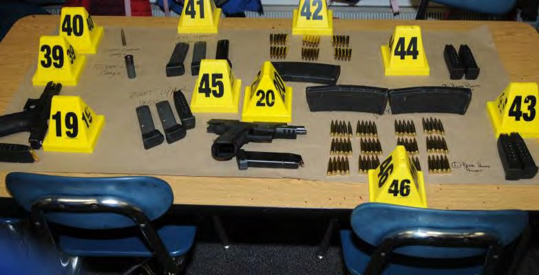 A table full of guns and ammunition