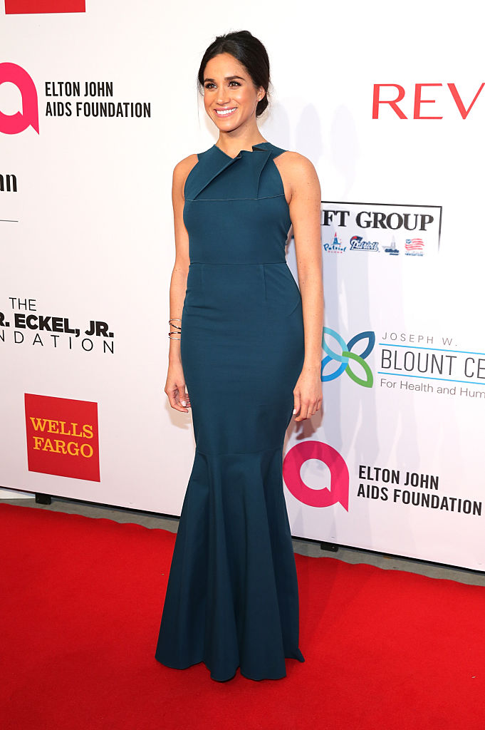 Meghan Markle poses on the red carpet in a blue gown.