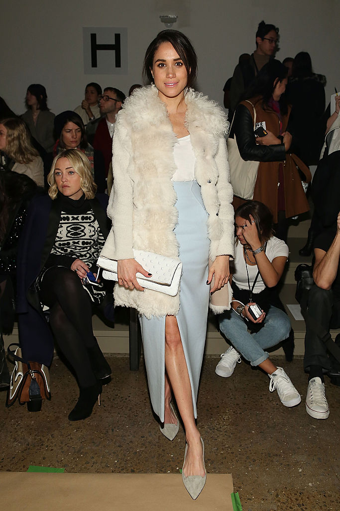 Meghan Markle posing in a fur coat in front of a crowd of people.