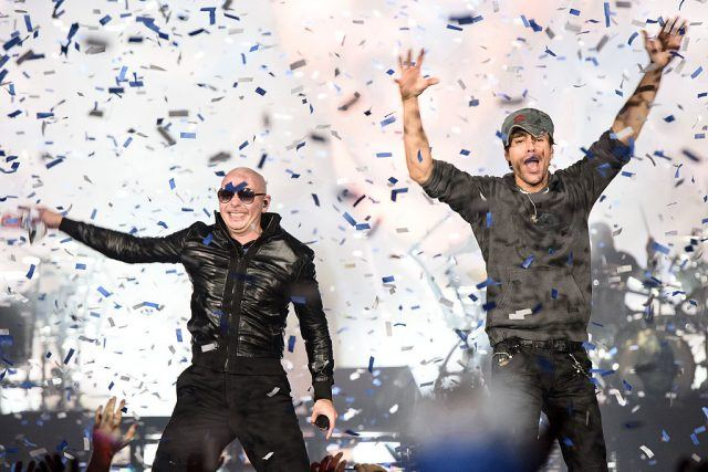 Enrique Iglesias and Pitbull dancing in graffiti on a white background.