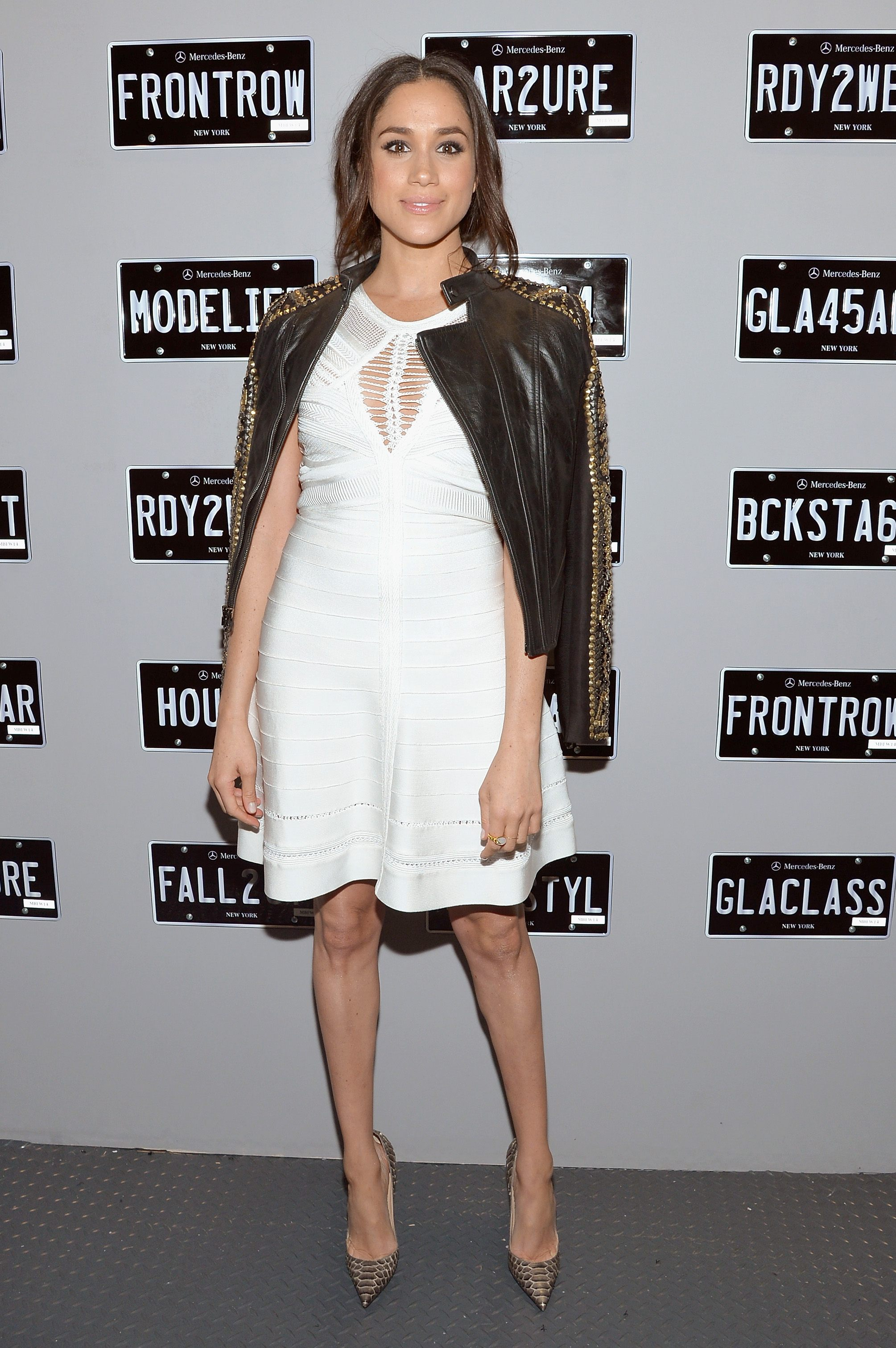 Meghan Markle posing in a white dress and black jacket.