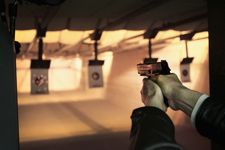 a gun owner sights a gun at a gun range