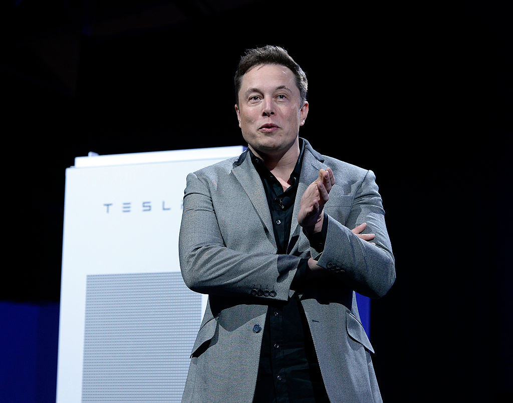 Elon Musk, CEO of Tesla, with a Powerpack unit the background