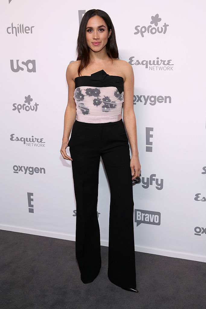 Meghan Markle posing on a gray carpet in a floral top and black pants