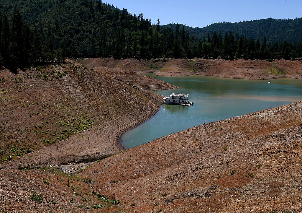 A lone houseboat beside an almost dry section of the Shasta Lake reservoir