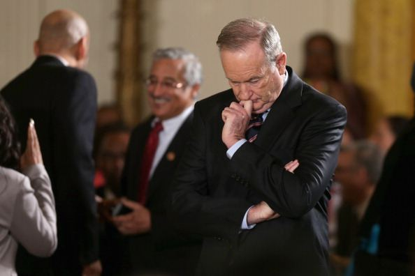 Bill O'Reilly in a dark suit looking thoughtful, surrounded by people