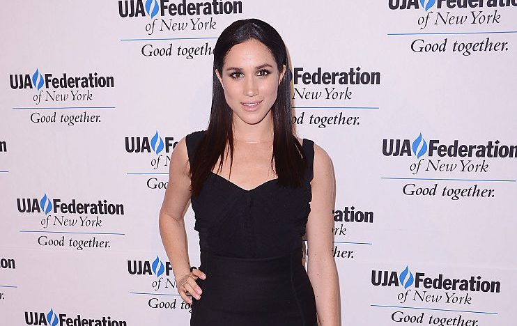 Meghan Markle posing in a black dress.