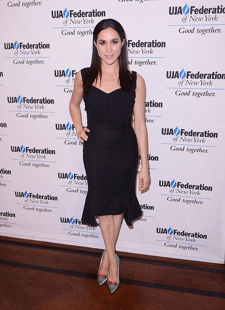 Meghan Markle posing in a black dress.