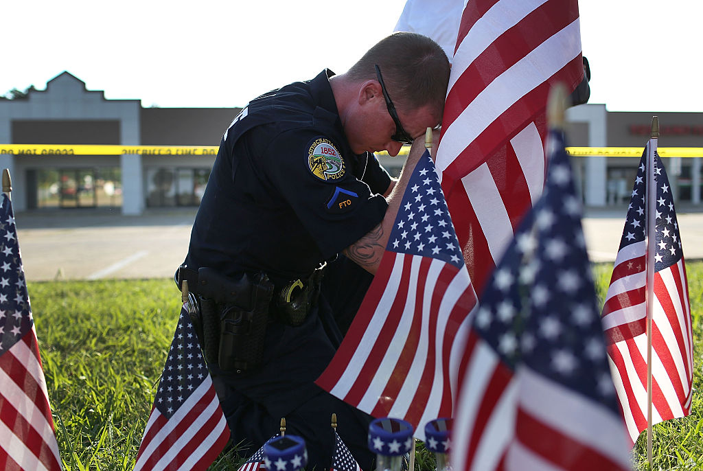 An officer on his knees places a flagamong many flags at the site of a memorial