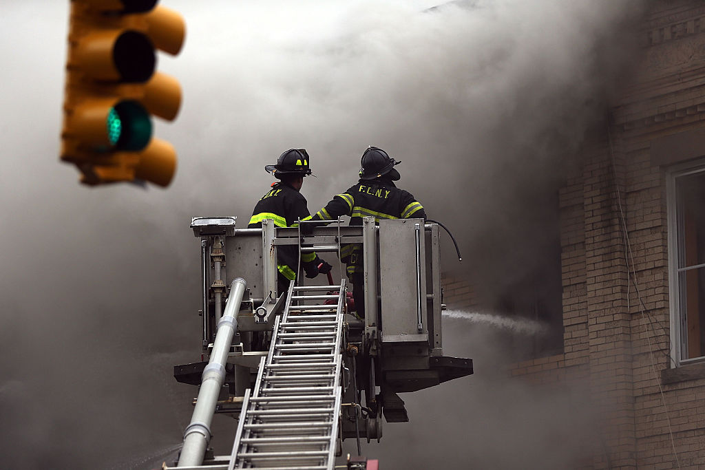 firefighters on a ladder in front of a building with smoke