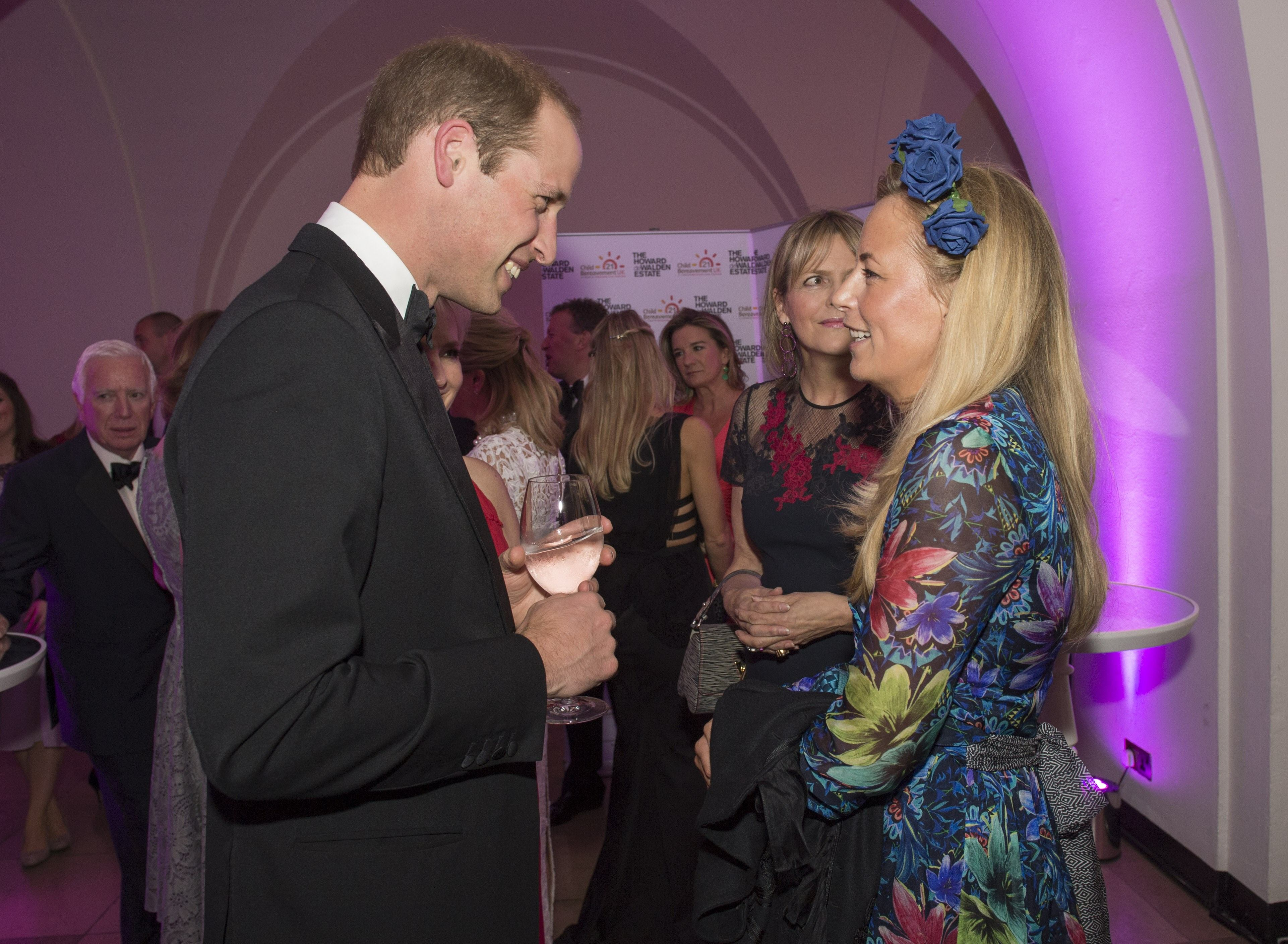 Britain's Prince William, Duke of Cambridge, (L) talks with guests Astrid Harbord during a charity dinner