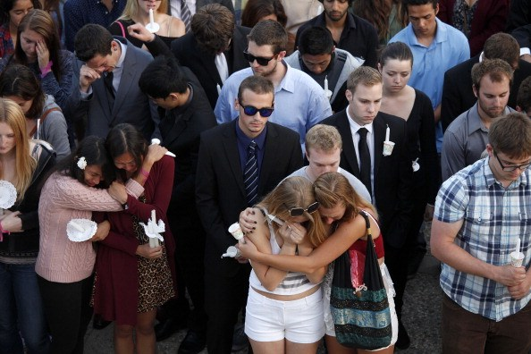 students hug and comfort each other on campus at Isla Vista