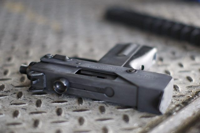 A small gun lays over a metal surface.