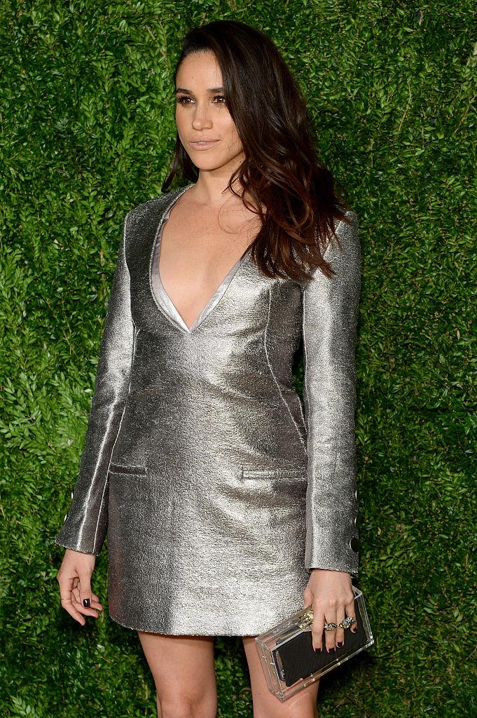 Meghan Markle posing in a silver dress in front of a leafy green backdrop.
